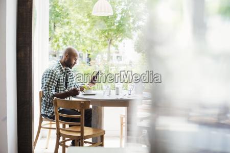 man wearing a checked shirt sitting