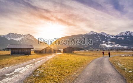 winter sonnenuntergang ueber alpinen landstrassen