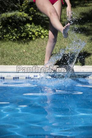 frau steht auf poolrand kicking wasser