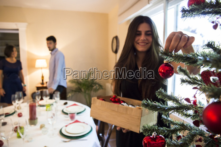 woman decorating the christmas tree with