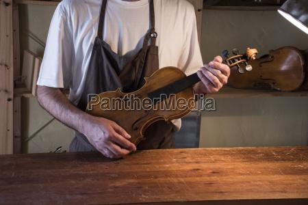 luthier haelt geige in seiner werkstatt