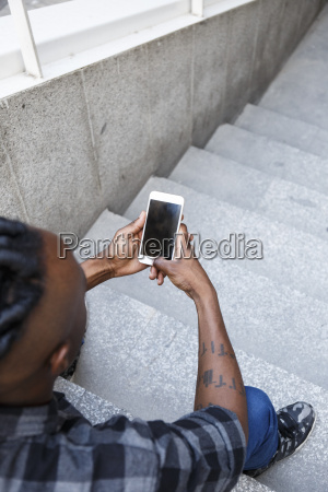 young man sitting on stairs using