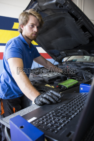 mechanic fixing a car engine while