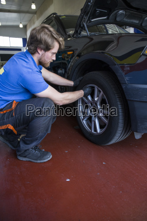 mechanic examining the wheel of a