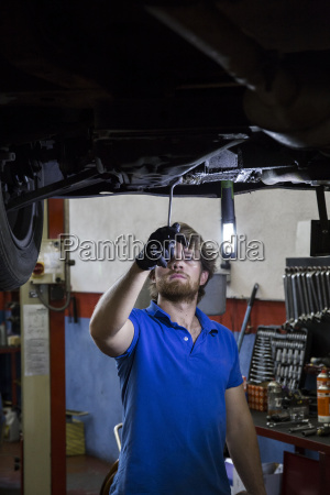 mechanic fixing suspended car in his