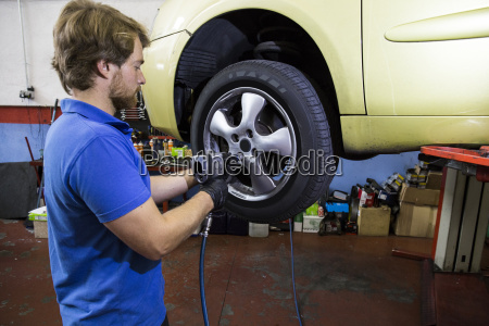 mechanic fixing a car wheel in
