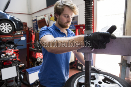 mechanic in car workshop exchanging tire
