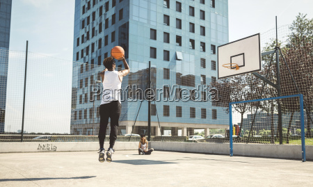 junger mann mit dem ziel basketballkorb