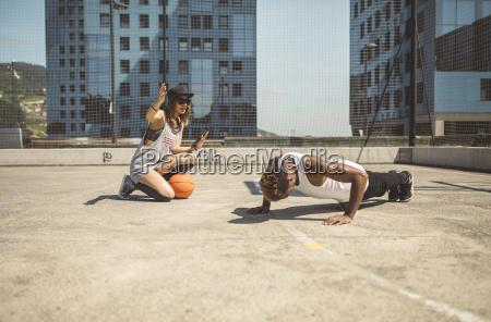 young woman coaching young man doing