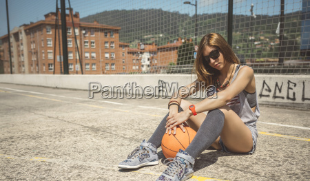 young woman sitting on ground of