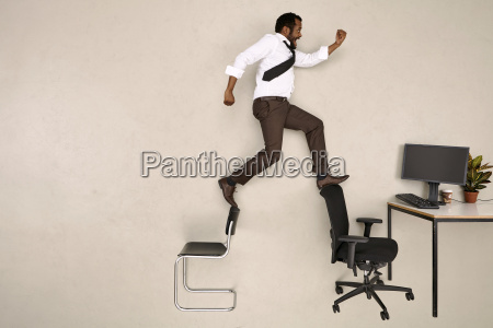businessman walking on chairs towards office