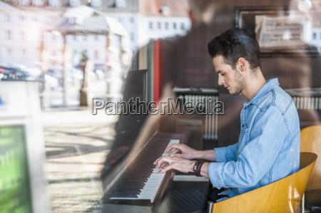 junger mann spielt klavier in einem