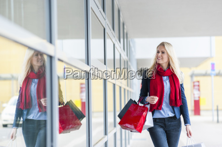 smiling woman with shopping bags passing