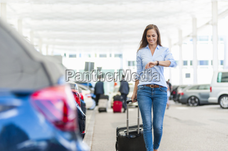 smiling woman walking with luggage on