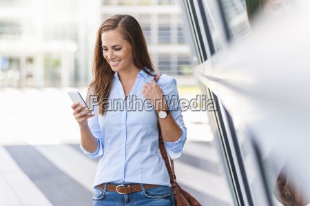 smiling woman looking at cell phone