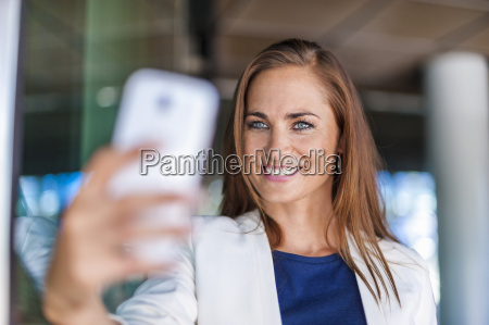smiling brunette woman holding cell phone
