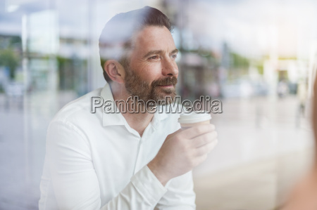 portrait of relaxed businessman looking through
