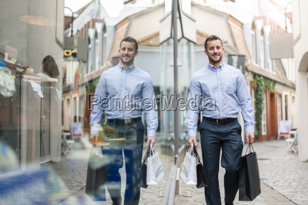 smiling young man with shopping bags