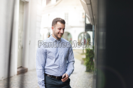 young man looking in shop window