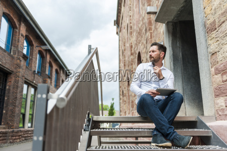 businessman with tablet sitting on stairs
