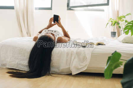 young woman lying in bed using