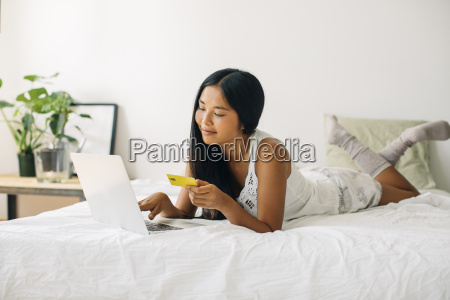 young woman lying in bed shopping