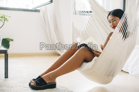 young woman sitting in hammock reading