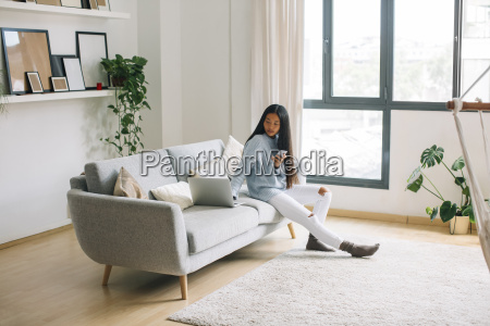 young woman with smartphone sitting on
