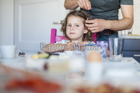 father doing daughters hair at breakfast