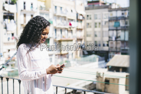 young businesswoman standing on balcony checking