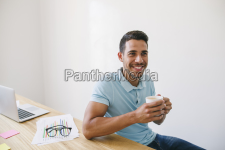 young man in office drinking coffee