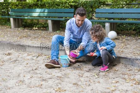 father playing with daughter in sandbox