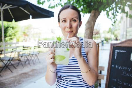 glueckliche frau trinkt hausgemachte limonade im