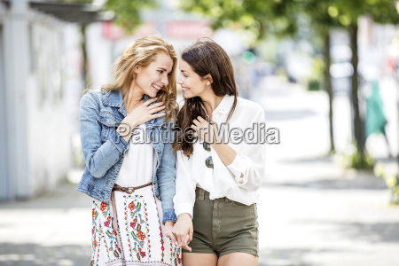 two smiling young women walking and