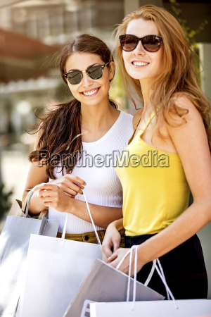 two smiling young women holding shopping