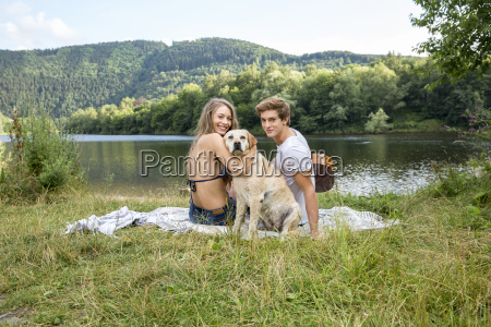 young couple with dog sitting at