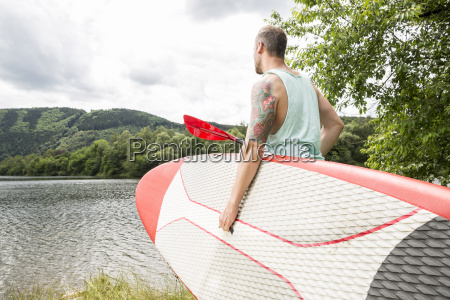 man carrying stand up paddle board