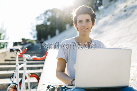 young woman with bicycle sitting outdoors