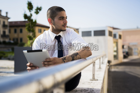 young businessman with tablet looking at