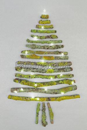 weihnachtsbaum in mooszweigen und weihnachtsdekoration