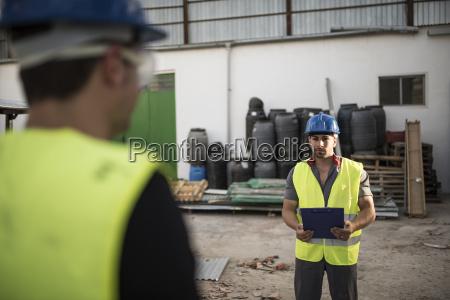 bauarbeiter sprechen und schauen notebook anweisungen