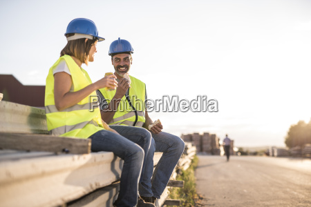 construction workers eating sandwich sitting on