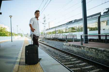 young man with suitcase waiting at