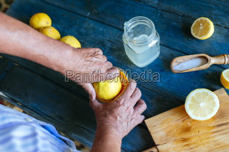 close up of hands squeezing lemons