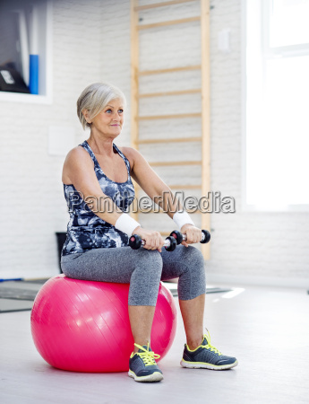 mature woman exercising with dumbbells on