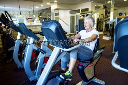 aeltere frau arbeitet in fitness studio