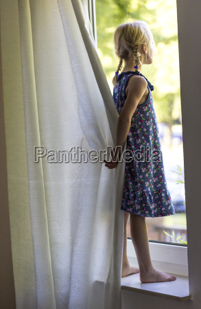 little girl standing on window sill