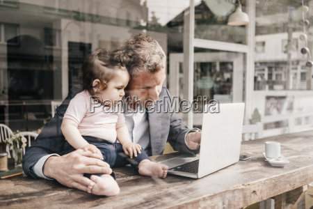 businessman with little daughter working on