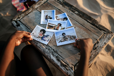 womans hands with instant photos on