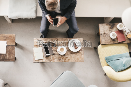 businessman sitting in cafe using smartphone